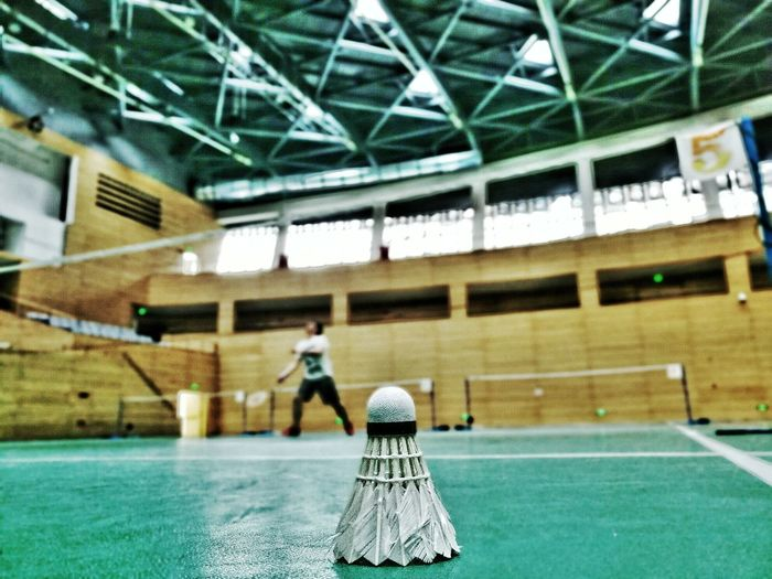 Shuttlecock against man playing badminton at court