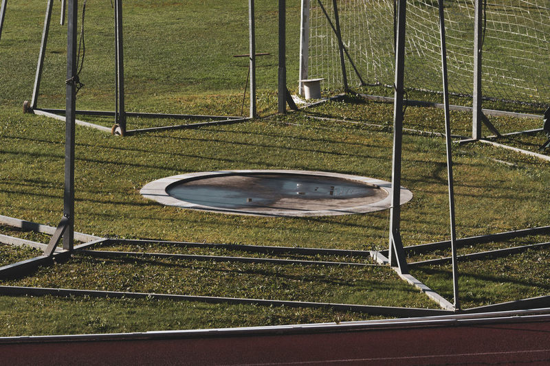 shot-put circle Playing Field Barrier Outdoor Play Equipment Grass Sport Plant High Angle View Nature No People Outdoors Absence Metal Green Color Sunlight Field Athletics Circle Cement Shot Put Weight Training Fitness Force Power Discipline