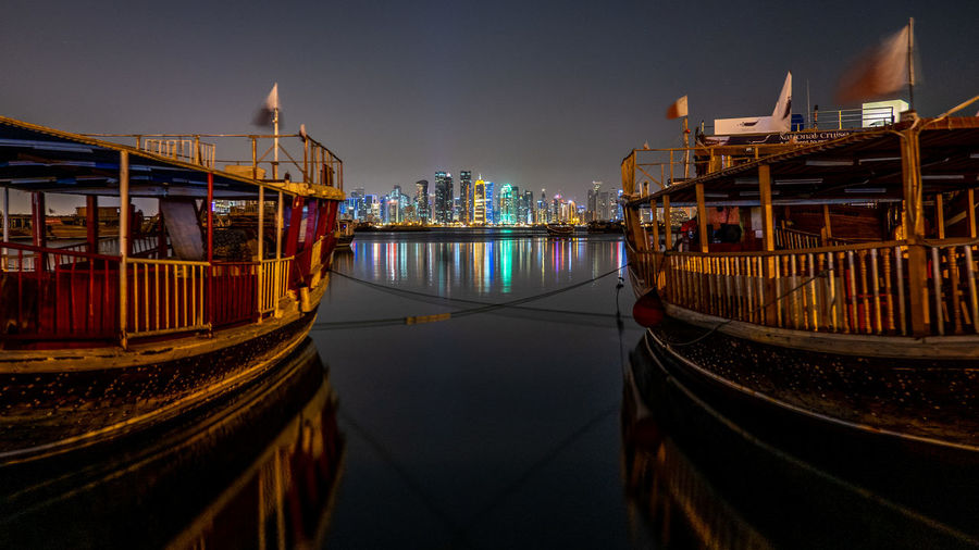 Panoramic view of illuminated buildings by river at night