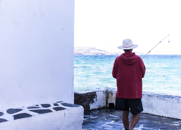 Solo fisherman on Mykonos Island Bright Day Candid Photography Candidphotography Candidshot Day Fishing Fishing Time Occupation One Man Only Outdoors Rear View Sea And Sky Seascape Seascape Photography Sky Standing Three Quarter Length Water_collection Waterfront Working