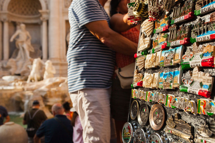 Tourist Souvenirs in Front of the Trevi Fountain in Rome, Italy Adult Choice One Person Retail  Lifestyles Standing Rear View Real People Variation Market Abundance Business Focus On Foreground Shopping Women Large Group Of Objects Midsection Day Trevi Fountain Rome Souvenir
