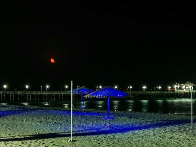 The Moon is screaming! Red Moon Red Moon Night Red Moon/ Eclipse Night Beach Photography Nightphotography Night Lights Beachphotography Beach Sand Marina Blue Lights  Umbrellas