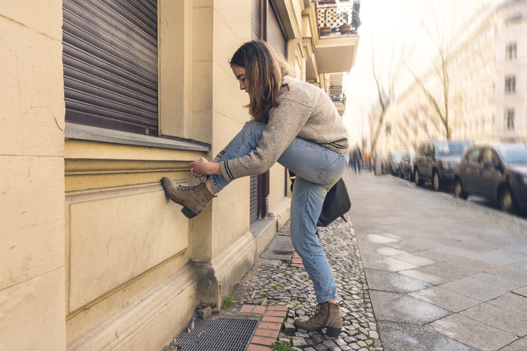 Full length of woman standing on footpath against buildings in city
