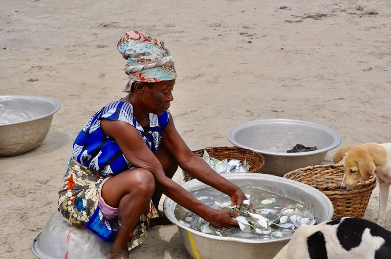 Woman sitting and separating fish into baskets for sale