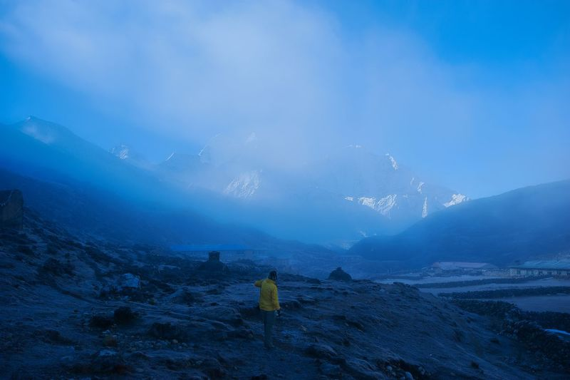 Rear View Of Person Standing On Snowcapped Mountains Against Sky