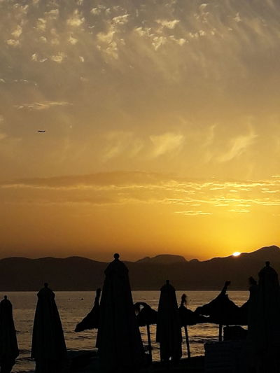 Silhouette Parasols At Beach Against Orange Sky