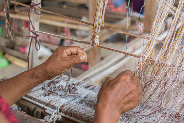 Close-up of worker holding thread while working on handloom