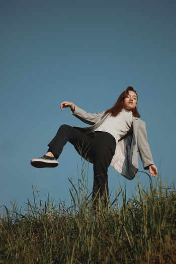 Low angle view of young woman standing on one leg over grass against clear blue sky