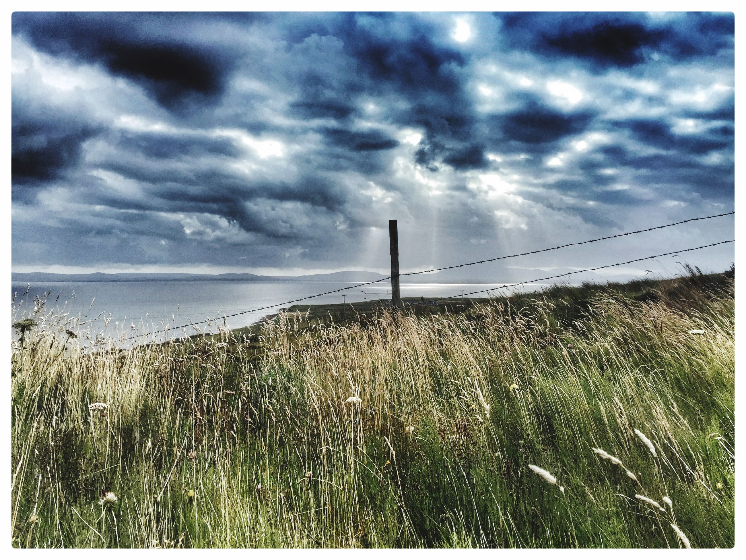sky, sea, cloud - sky, horizon over water, water, cloudy, transfer print, tranquil scene, tranquility, scenics, auto post production filter, cloud, beauty in nature, nature, beach, grass, overcast, shore, weather, built structure