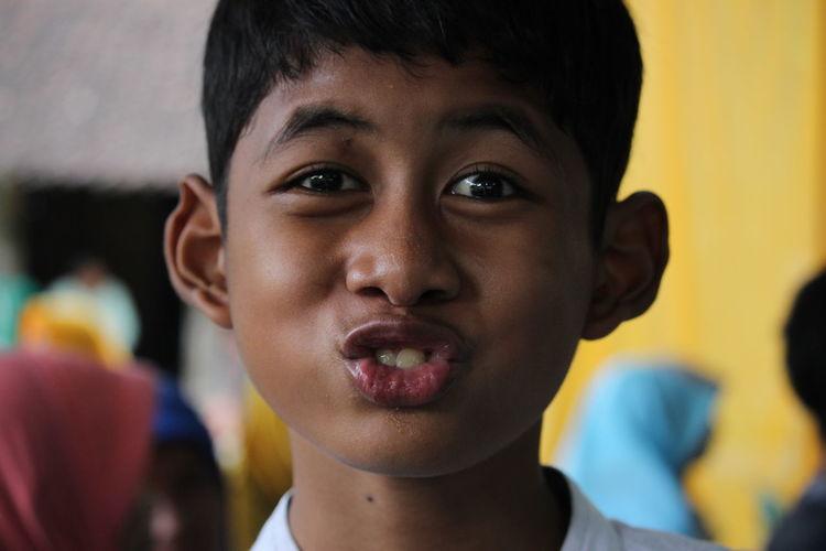 Close-up portrait of boy making face