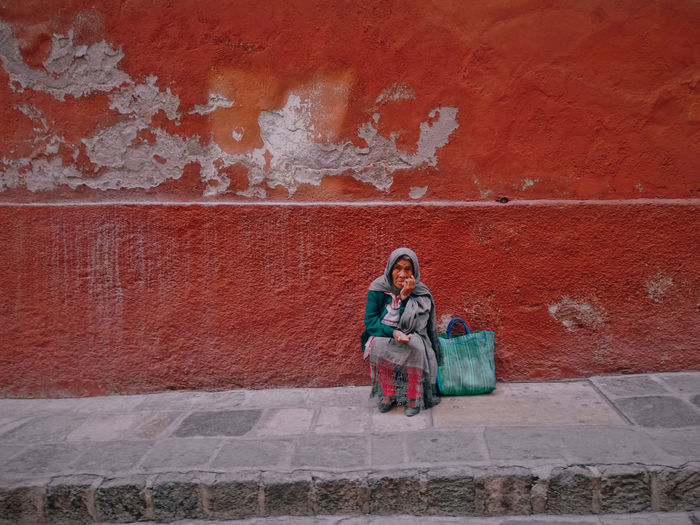 Female beggar sitting against red wall on sidewalk