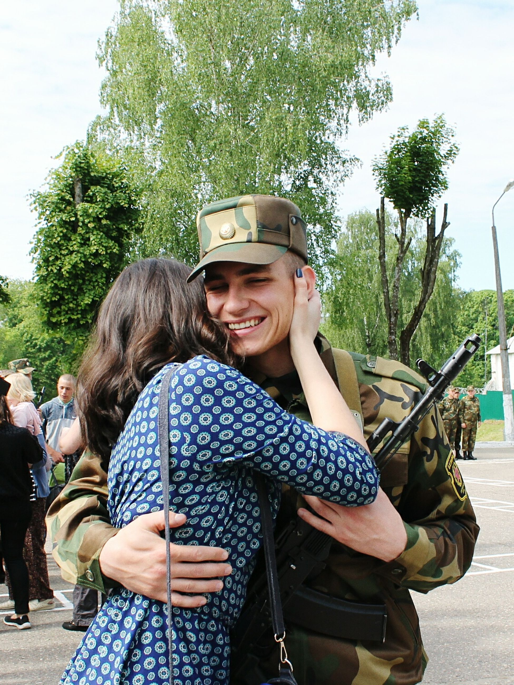 two people, young women, real people, togetherness, young adult, leisure activity, tree, lifestyles, day, standing, happiness, young men, love, smiling, backpack, embracing, men, couple - relationship, women, bonding, technology, outdoors, portrait, military, camouflage clothing, adult, people