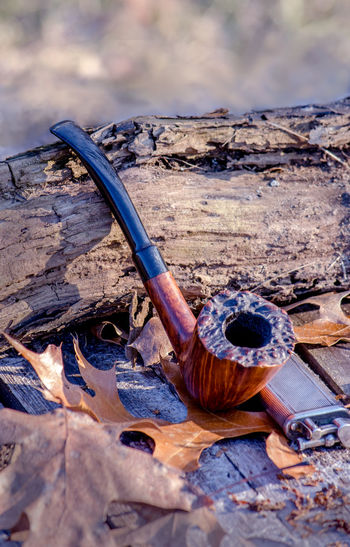 Close-up of smoking pipe and cigarette lighter by wood