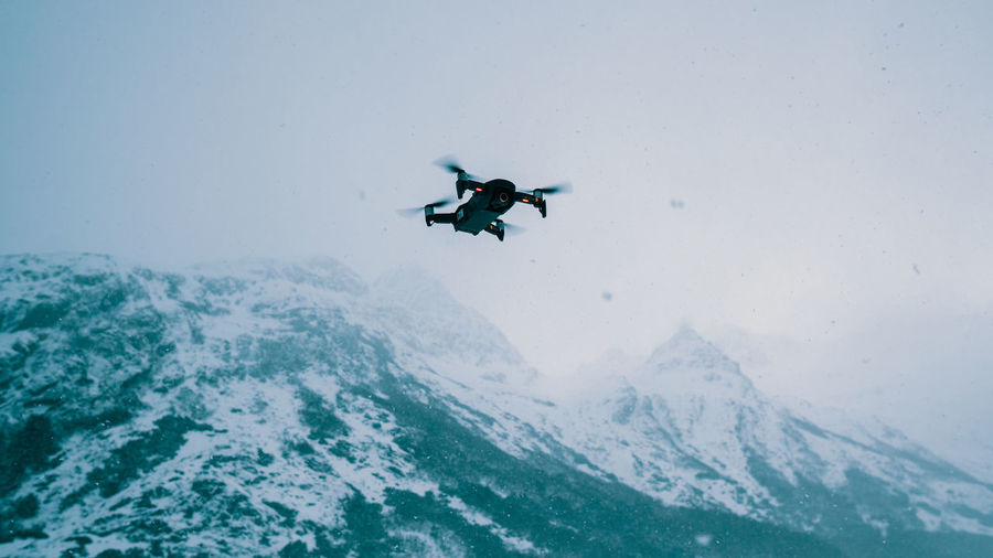 Low angle view of person skiing on snowcapped mountain