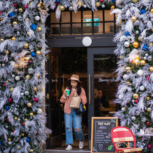 Woman standing by christmas tree
