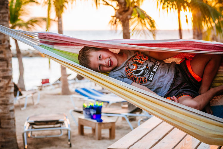 Young boy together in a hammock on the beach at blue bay in willemstad curacao Beach Curacao Day Leisure Activity Lifestyles One Person Only Men Outdoors Palm Tree People Portrait Smile Smiling Smiling Face Vacations Young Adult