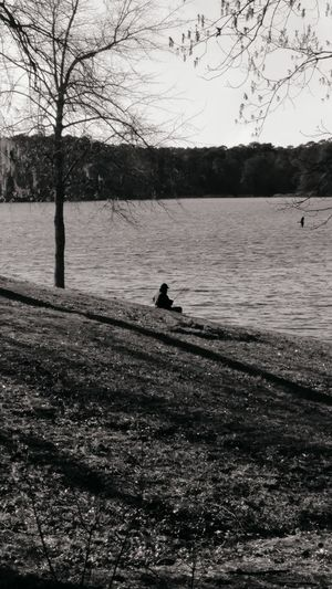 Silhouette man on riverbank against sky