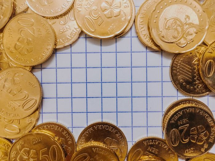 Gold coin over the grid paper Metal Token Coin Gst Gold Colored Gold No People Wealth Close-up Indoors  Day