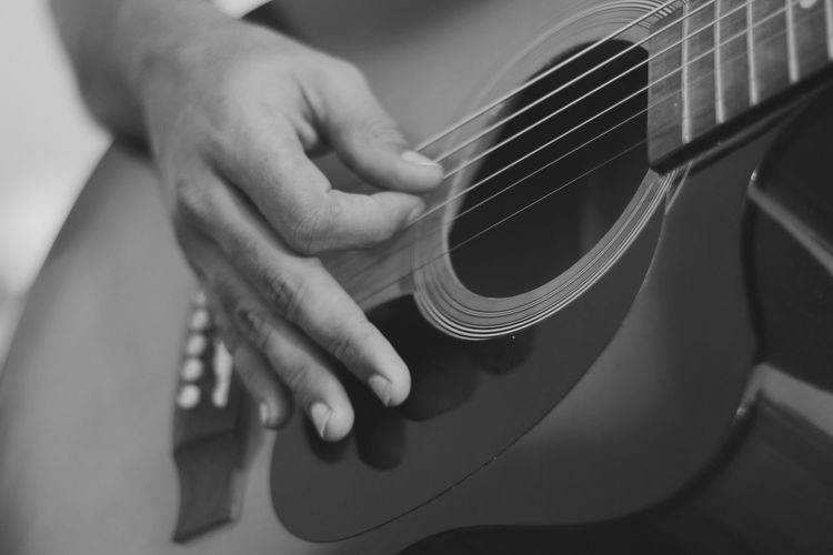 Cropped image of hand playing guitar