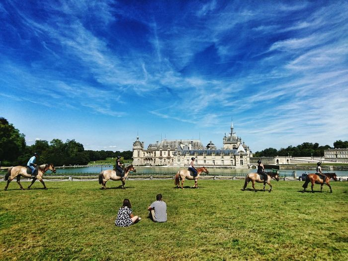 Couple looking at people riding horses at chateau de chantilly