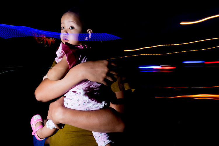 Full length of woman looking at illuminated nightclub