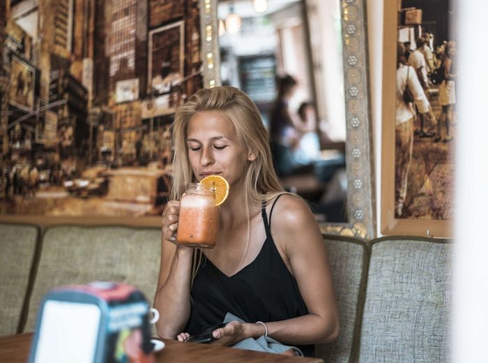 Midsection of a woman drinking glass at restaurant