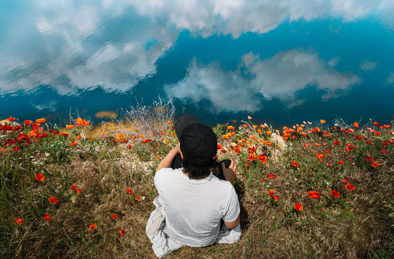 Man sitting in poppy field by the lake with clouds reflection