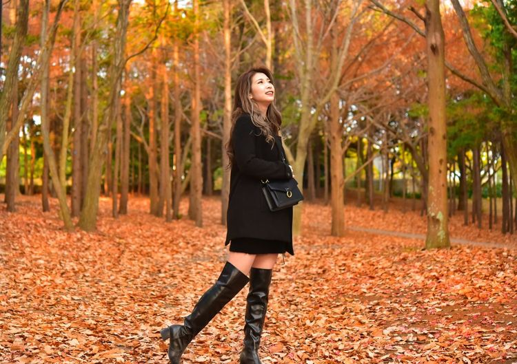 Full length of young woman standing in autumn leaves