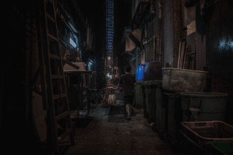 Rear view of man walking on footpath amidst buildings at night