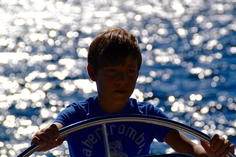 Boy Steering Boat Against Sea On Sunny Day