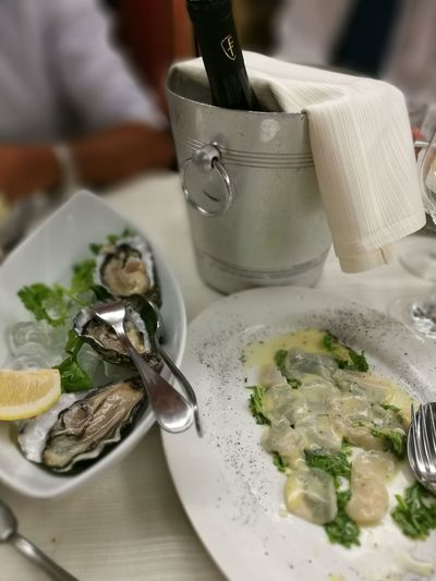 Seafood With Wine Bottle On Table At Restaurant