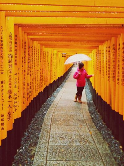 Woman With Umbrella Standing On Pathway At Fushimi Inari Shrine
