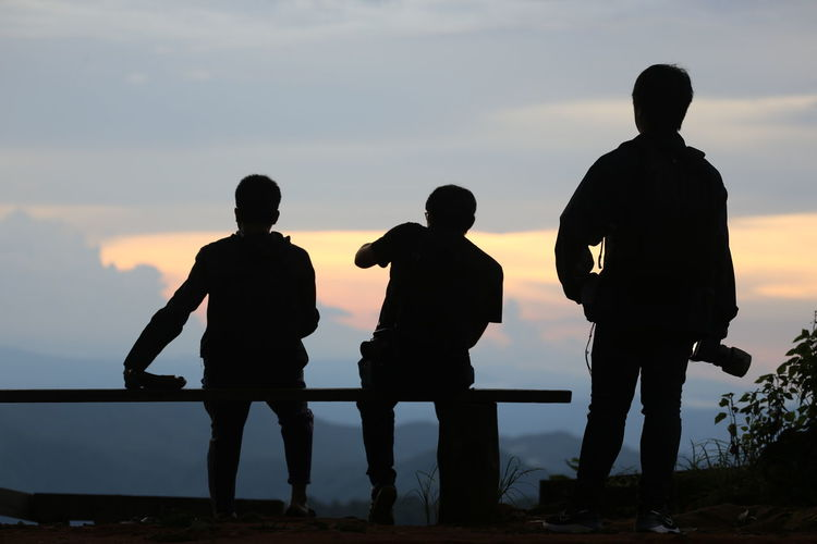Silhouette people looking at sea against sky