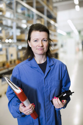 Portrait of smiling woman standing in factory