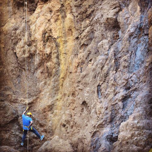 Rear view of man climbing rock