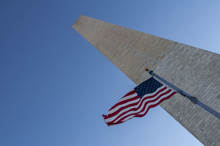 Low angle view of american flag and washington monument against clear blue sky