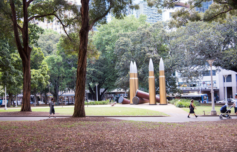 "Sydney,NSW,Australia-November 18,2016: Hyde Park with ""Thou didst let fall"" aboriginal war memorial and tourists in downtown Sydney, Australia. Aboriginal Art Installation ArtWork City Life Golden Hyde Park, Sydney Memorial Public Transportation Sidewalk Sydney, Australia Tree War Memorial Art Bullet Bus Hyde Park Leisure Activity Military Public Art Public Places Real People Sculpture Shells Visual Statements Walking"