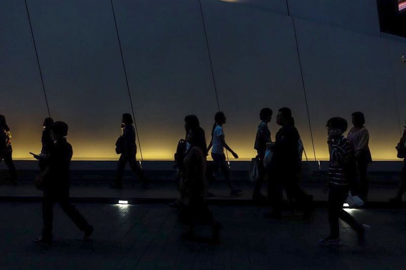 Silhouette people standing against sky at dusk