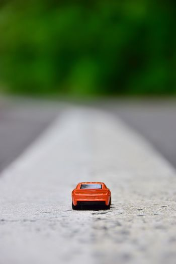 EyeEm Selects Transportation Toy Car Toy Car No People Road Mode Of Transportation Focus On Foreground Nature Green Color Outdoors Land Motor Vehicle Day Still Life Selective Focus Red Sunlight The Way Forward Surface Level