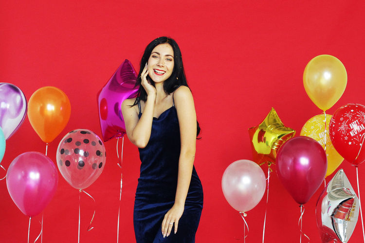 Full length of a smiling young woman with red balloons
