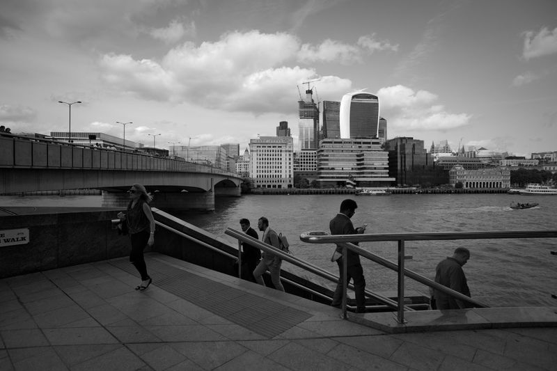 People on bridge over river in city against sky