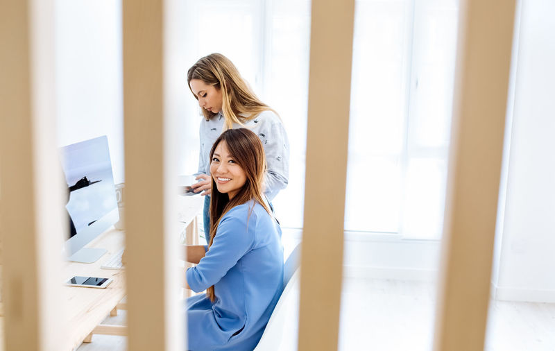 Smiling woman with colleague at desk in office