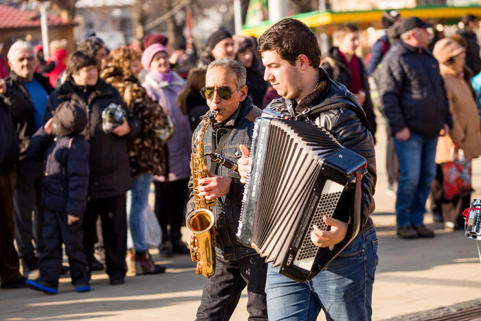 PERNIK, BULGARIA - JANUARY 26, 2018: Old street musician with white hair and sunglasses plays saxophone while walking at the annual International Festival of Masquerade Games Surva in Pernik, Bulgaria SaXoPhOnEs Sax Saxophonist Accordion Adult Adults Only Arts Culture And Entertainment City Crowd Day Focus On Foreground Large Group Of People Men Music Musical Instrument Musician Outdoors People Performance Playing Real People Saxophone Saxophone Player Saxophonelife Street