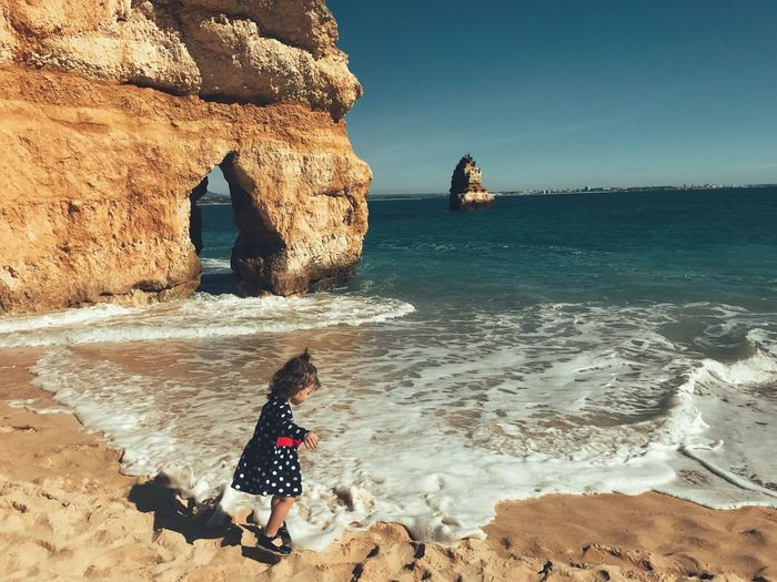 Girl Standing On Shore At Praia Do Camilo Against Rock Formation