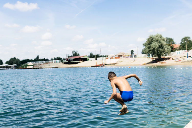 Full length of shirtless boy diving in sea against sky