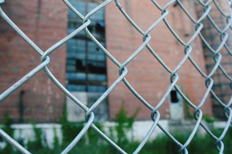 Close-Up Of Chainlink Fence Against Building