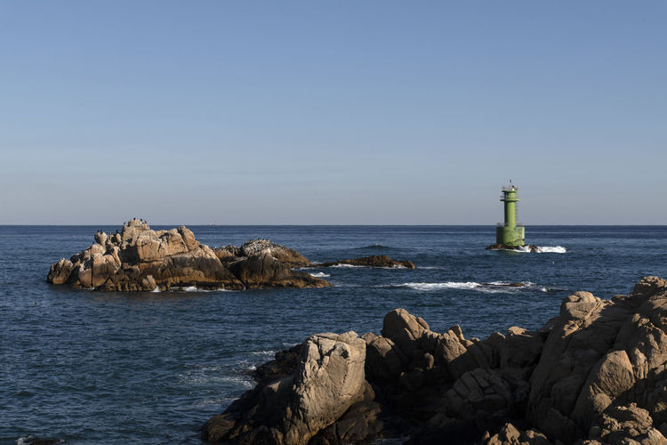 Lighthouse On Rock By Sea Against Clear Sky
