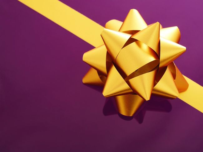 Gift bow Shiny Gold Gift Bow Birthday Nobody Gift Bow Present Indoors  Paper No People Still Life Ribbon Gift Bow Colored Background Purple Ribbon - Sewing Item Close-up Tied Bow High Angle View Copy Space Christmas