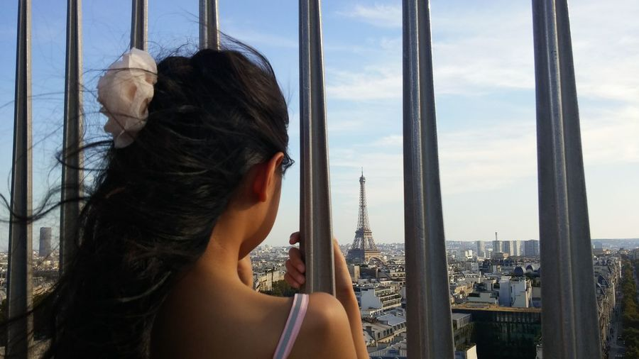 Rear view of girl looking at eiffel tower in city seen through fence