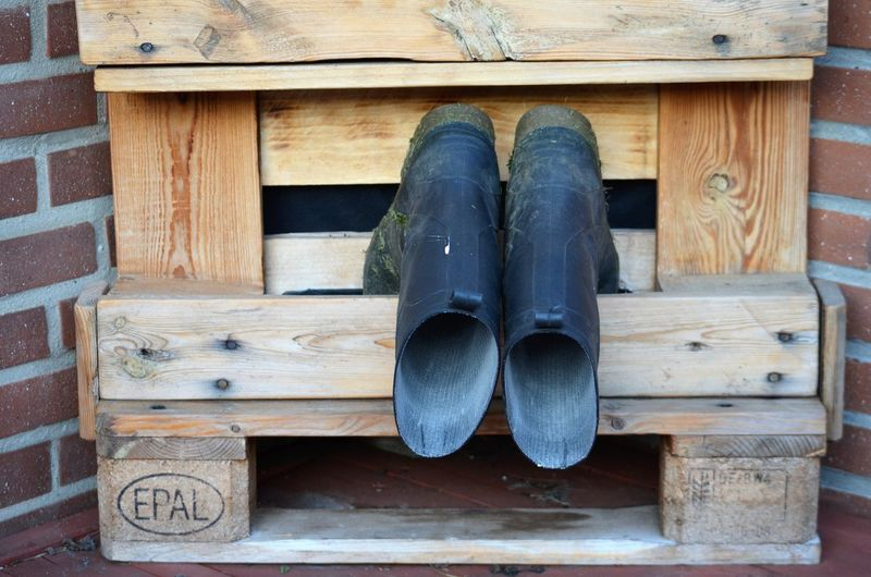 Low section of shoes on wooden wall